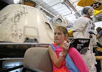 Macy Cleveland, then 7, of Royce City, filled out a Moon Day work book in front of the Apollo 7 capsule during a Moon Day event at the Frontiers of Flight Museum in Dallas in 2016.(Stewart F. House/Special Contributor)
