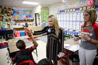 First grader Calen Simms, 6, gives principal Aimee Lewis a high five after correctly answering a math problem at McKenzie Elementary School in Mesquite, Texas on December 5, 2017. Lewis has been working in the Mesquite district for the past 28 years. First grade teacher at right is Logan Cornelison.(Vernon Bryant/Staff Photographer)