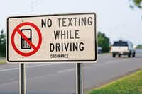 Close up of no texting while driving ordinance sign with vehicle in background.(sshepard/Getty Images)