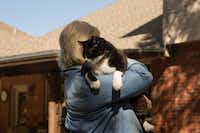 Sally Kilgore plays with her cat, Bob, who is known to prowl the garden.(Shaban Athuman/Staff Photographer)