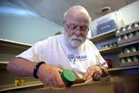 """Dan Carlson packs a """"gap bag"""" for someone at WestAid, a food pantry, in Fort Worth on Oct. 10, 2018 where Dan and his wife Bonnie Connie volunteer.(Daniel Carde/Staff Photographer)"""