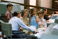 Astronauts' wives Pat White (right) and Pat McDivitt (left) and the Whites' children, Bonnie  and Eddie III, visit Mission Control and sit with flight director Chris Kraft, during Gemini 4 (during which  Ed White performed the first U.S. spacewalk), in June 1965.  NASA image provided by Grand Central Publishing.