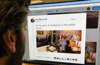 An editor looks at the Twitter feed of Josh Billinson showing a painting by Andy Thomas titled <i>The Republican Club</i>alongside a screen shot of the paintinghanging at the White House during a <i>60 Minutes</i> interview with President Donald Trump.(Mario Siranosian/Agence France-Presse)
