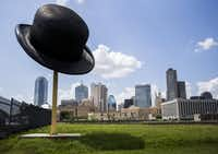 A sculpture of a giant bowler hat by Keith Turman is seen with the Dallas skyline behind it at the intersection of Griffin Street East and South Ervay Street in the Cedars neighborhood. (Ashley Landis/Staff Photographer)