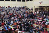 Immigrants, part of the Honduras  migrant caravan of more than 1,500 people, rest for the night in a community gym on October 16, 2018 in Chiquimula, Guatemala. (John Moore/Getty Images)