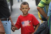 David Cortez, age 7, waits with his father to catch a ride as part of a migrant caravan headed toward the United States on October 17, 2018 in Zacapa, Guatemala. (John Moore/Getty Images)