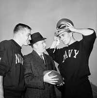 Navy coach Wayne Hardin (center) talks with his star quarterback, Roger Staubach (right), in final workout in Philadelphia Stadium on Dec. 7, 1963, before annual battle against Army, with center Tom Lynch listening in.(Bill Achatz/The Associated Press)