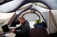 Todd Phillips, founder and director of the Last Well, prepares to record a Facebook Live video from inside his tent on his wooden barge on Lake Ray Hubbard in Rockwall. (Rose Baca/Staff Photographer)