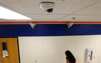 A student passes one of the new security cameras in a hallway near two of the older models at McKinney North High School.(Vernon Bryant/Staff Photographer)