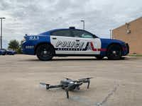 An unmanned aircraft used by Arlington Police in front of an Arlington squad car. The Arlington Police Department began operating drones in 2013.(Arlington Police Department)