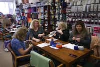 From left, Lee DeVine of Plano, Yarn and Stitches owner Hope Logan, Barbara Thomas and Alysha Henry talk about how relaxing knitting can be while they make butterfly shawls during a workshop at the knitting store.(Daniel Carde/Staff Photographer)