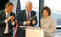 Dallas Mayor Mike Rawlings (left) and U.S. Sen. John Cornyn joined U.S. Secretary of Transportation Elaine Chao to talk about the airport improvement grants as she presented a letter of intent for DFW International Airport infrastructure improvements, including end-around taxiways, in July.(Louis DeLuca/Staff Photographer)