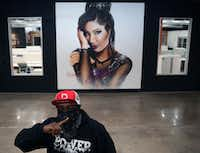 Artist Theo Ponchaveli in front of a Selena artwork. Ponchaveli, who normally covers his face while painting to protect from fumes, said people usually see him wearing a bandanna so he wears it in photographs. His first Selena mural was on his previous studio in Oak Cliff.(Daniel Carde/Staff Photographer)