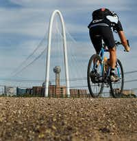 A cyclist makes his way along a path on the levee off of Canada Drive in West Dallas. (Louis DeLuca/Staff Photographer)
