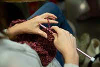 At Spreading the Warmth's monthly Knit Night, a participant works on a scarf. (Allison Slomowitz/Special Contributor)