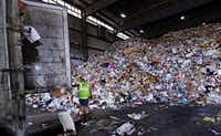 A trailer door is opened on a truck filled with unsorted recyclable trash as it is offloaded and added to a giant pile in a processing building in Westborough, Mass. Recycling programs across the United States are shutting down or scaling back because of a global market crisis blamed on contamination at the curbside bin.(2008 File Photo/AP)