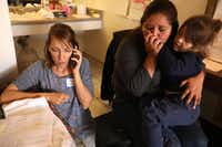 Annunciation House volunteer Rachel Soltis (left) gets in touch with Leslie Angelia's family in Los Angeles to arrange a bus ticket for her and her daughter Argelee Yulieth, 3, a day after the pair were released from detention at a motel in El Paso, Texas, on October 23, 2018. (Genaro Molina/TNS)
