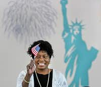 Elizabeth Evans, from Zambia, happily waves a miniature American flag as she becomes an American citizen at a naturalization ceremony in May 2018.(Louis DeLuca/Staff Photographer)