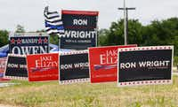 Competing signs for US Congressional candidates in District 6 stand outside the Ellis County Courthouse in Ennis, Texas on Monday May 14, 2018 for primary voting.(Guy Reynolds)
