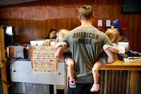 Lee Grounds of Barry, Texas, holds his twin 2-year-old daughters Leighton (left) and Langston while waiting on his order at Flores Barbecue in Whitney. He says he regularly drives more than 40 miles for the barbecue.(Tom Fox/Staff Photographer)