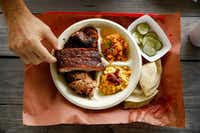 "<p>Pork ribs, pulled pork and brisket are served with a side of&nbsp;<span style=""font-size: 1em; background-color: transparent;"">jalapeño&nbsp;</span><span style=""font-size: 1em; background-color: transparent;"">corn, Spanish rice (only available on Saturdays), spicy pickles and homemade tortillas at Flores Barbecue in Whitney.&nbsp;</span></p>(Tom Fox/Staff Photographer)"