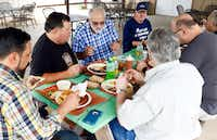 Texas BBQ Posse founding members Chris Wilkins (second from left) and Gary Jacobson (third from left) try different meats at Flores Barbecue.(Tom Fox/Staff Photographer)