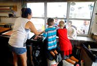 Brandi Alejandro (left) helps Elliot Guess (center) and Ryan Hayes take orders at the trailer window of Guess Family Barbecue in Waco. Guess, 7, is the son of the owners.(Tom Fox/Staff Photographer)
