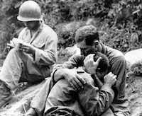 An American infantryman weeps on the shoulder another GI after his buddy was killed in action in the Korean War in this Aug. 28, 1950, file photo.(Al Chang/The Associated Press)