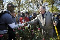 Former President George W. Bush shakes hands and thanks veteran Navy submarine officer Joshua Stewart, who was planting dogwood trees during a Veterans Day landscaping project Sunday in Philadelphia's Point Breeze neighborhood.  Stewart is part of a group of veterans who serve as Character Does Matter mentors for the Travis Manion Foundation. (Tom Fox/Staff Photographer)