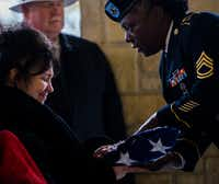 """Eva Arnold is presented with an American flag that was draped on a casket containing the remains of Army Corporal Albert """"Buddy"""" Mills at Dallas-Fort Worth National Cemetery on Monday, November 12, 2018. Mills was Arnold's uncle.(Ashley Landis/Staff Photographer)"""