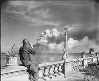 An American soldier watches Manila burn from the beach at Paranque on Feb. 8, 1945. From <i>Rampage: MacArthur, Yamashita and the Battle of Manila</i>, by James M. Scott.(National Archives and Records Administration)