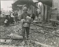 An American soldier carries a wounded girl to a boat landing in preparation to evacuate the ruins of Manila's Walled City on Feb. 23, 1945. From <i>Rampage: MacArthur, Yamashita and the Battle of Manila</i>, by James M. Scott.(National Archives and Records Administration)