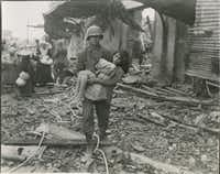 An American soldier carries a wounded girl to a boat landing in preparation to evacuate the ruins of Manila's Walled City on Feb. 23, 1945. From <i>Rampage: MacArthur, Yamashita and the Battle of Manila</i>, by James M. Scott.&nbsp;&nbsp;(National Archives and Records Administration)