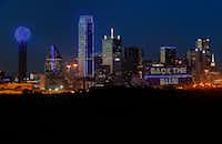 The skyline of Dallas is aglow in blue on July 7, 2017 to remember the four Dallas police officers and one Dallas Area Rapid Transit officer killed in the 2016 police ambush.(Tom Fox/Staff Photographer)