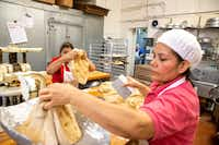 Laura Anaya, foreground, weighs dough as Lupita Arrona, middle, cuts it into equal size while owner Alfonso Vera, background, bakes at Vera's Bakery Inc. in Dallas on Nov. 13, 2018. (Shaban Athuman/Staff Photographer)