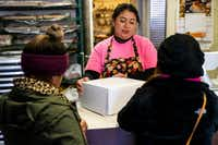 Naomi Vera Chavarria center, helps customers purchase a birthday cake at Vera's Bakery Inc. in Dallas on Nov. 13, 2018. (Shaban Athuman/Staff Photographer)
