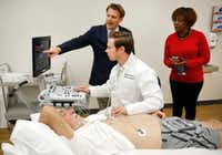 """<p><span style=""""font-size: 1em; background-color: transparent;"""">Michael D. Nelson, Applied Physiology and Advanced Imaging Laboratory director, points to the screen to show Phyllis Miller how Ph.D. student Jake Samuel is performing an ultrasound reading on volunteer Bill McNeill's heart during a tour at the University of Texas-Arlington this fall.</span></p>(Tom Fox/Staff Photographer)"""
