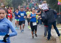 A runner high-fives a member of the crowd at the 8-mile mark of the 2016 BMW Dallas Marathon.(Stewart  F. House/Special Contributor)