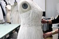 A David's Bridal employee arranges a dress on a plus-size mannequin in New York.(Bebeto Matthews/AP)