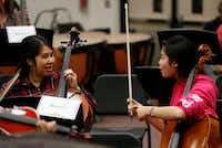 Monica Chi gets some instructional help from her daughter Julianne Chi, 14, during a practice for parents of students at Liberty High School in Frisco on Nov. 7.  (Vernon Bryant/Staff Photographer)