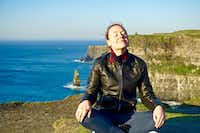 Lauren McGaughy meditates near the edge of the Cliffs of Moher, with O'Brien's Tower off in the distance.(J. David McSwane/Staff)