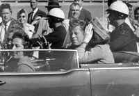 In this Nov. 22, 1963 file photo, President John F. Kennedy waves from his car in a motorcade in Dallas. Riding with Kennedy are First Lady Jacqueline Kennedy, right, Nellie Connally, second from left, and her husband, Texas Gov. John Connally, far left. (Jim Altgens/AP)