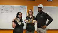 At Evantage, the competition is fierce for the  WWF championship belts they can earn for being tops in sales. Celebrating wins are (from left) Hannah Magnuson, a corporate trainer, Courtney Taylor, a former intern account rep, and Anthony Hubbard, a senior corporate trainer.(Evantage)