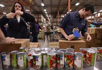 'A Christmas Carol' artistic director Kevin Moriarty (right) and Rachel Hull, director of education and community engagement for the Dallas Theater Center, volunteer at the North Texas Food Bank in Dallas on Dec. 12, 2014. (Rose Baca/Staff photographer)
