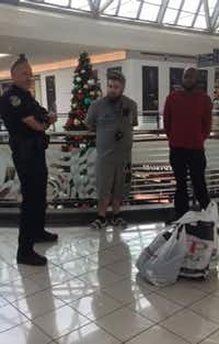 Brandon Kibart (center) and Ro Lockett (right) talk with a Frisco police officer after they were handcuffed and accused of shoplifting at Stonebriar Mall on Nov. 21, 2018.(youtube.com)