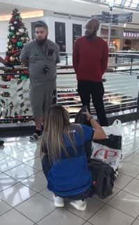 A Finish Line employee goes through bags of items purchased by Ro Lockett (right) and Brandon Kibart (left) at Stonebriar Centre in Frisco.(youtube.com)