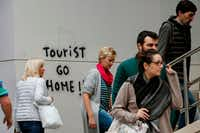 "Visitors  walked past graffiti reading ""Tourist go home!"" on their way to Park Guell in Barcelona in November. (Pau Barrena/Agence France-Presse/Getty Images)"