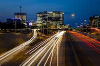 A long exposure shows traffic on the Dallas North Tollway at Tennyson Parkway with Legacy West, Liberty Mutual, and The Shops at Legacy development in Plano. (Smiley N. Pool/Staff Photographer)