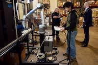 An All Axis Machining employee programs a robot with an OnRobot electric gripper to conduct a task in the Dallas machine shop.(Ben Torres/Special Contributor)