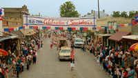 """<p></p><p><i>True Stories</i>' """"Celebration of Specialness"""" parade sequence was<span style=""""font-size: 1em; background-color: transparent;"""">filmed on North Tennessee St. in McKinney. In the movie,</span><span style=""""font-size: 1em; background-color: transparent;"""">David Byrne plays a visitor to the fictional small Texas town of Virgil who has an unusual dinner with a civic leader (Spalding Gray) and his family.</span></p>(Warner Bros.)"""